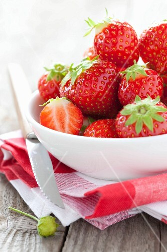 Fresh strawberries in a bowl and fruit knife on tea towel