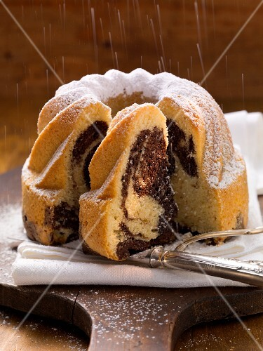 Dusting a vanilla and chocolate bundt cake with icing sugar