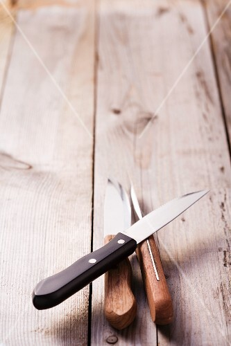Three steak knives on a wood background