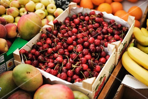Crate of cherries and other fruits on a fruit stall