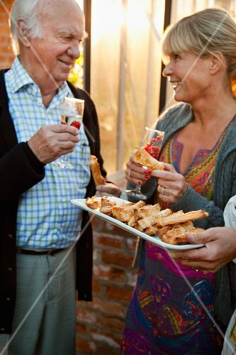 Older couple with cheese straws and sparkling wine cocktails