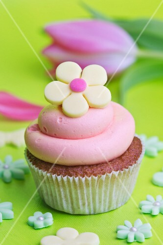 A cupcake with strawberry cream and a yellow sugar flower