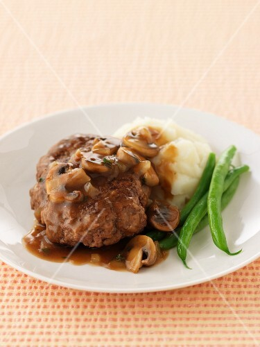 A burger with mushroom sauce, mashed potatoes and green beans