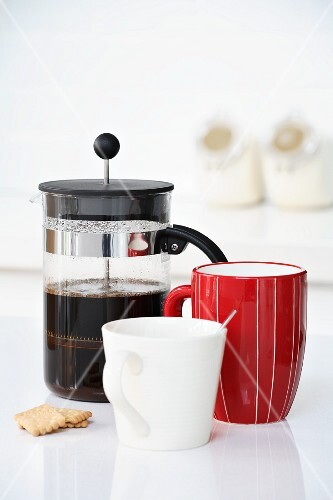 Coffee in cafetiere, red mug and white cup