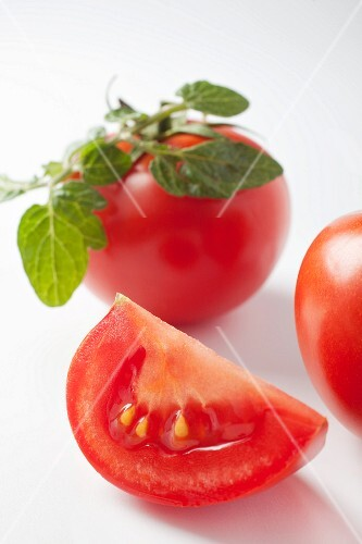 A slice of tomato and a whole tomato with leaves