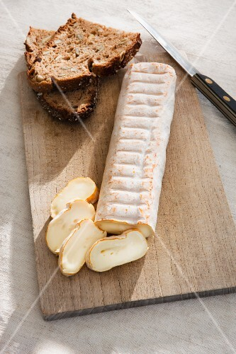 Sliced soft cheese with dark bread