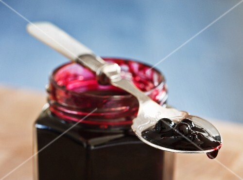 Blueberry jam on a spoon on a glass
