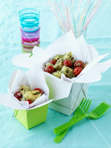 Potato salad with cherry tomatoes in a take-away box