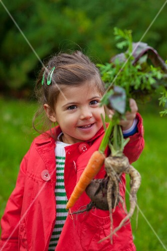 Little girl holding assorted root vegetables in her hand