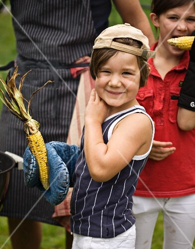 Children with grilled corn cobs