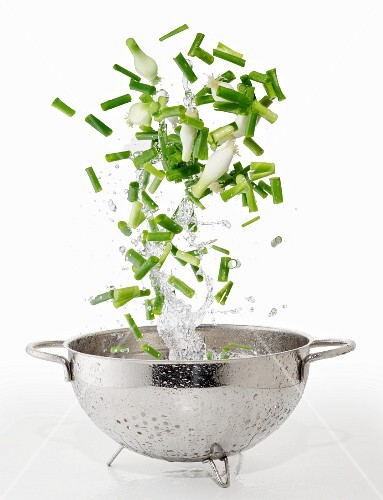 Spring onions and splash of water falling into a colander