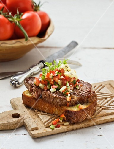 Toasted bread topped with beef steak and tomato salsa