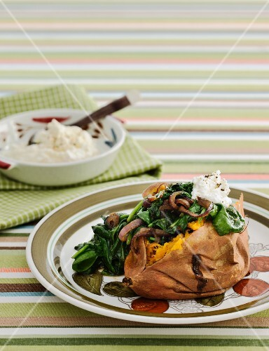 Baked sweet potato with feta, spinach and red onions