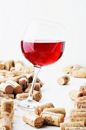 A glass of red wine with corks