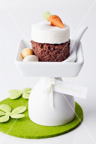 A sponge cake topped with meringue and a marzipan carrot and served with sugar Easter eggs
