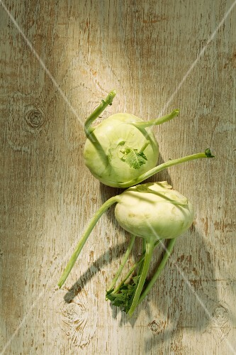 Two kohlrabis on a wooden surface