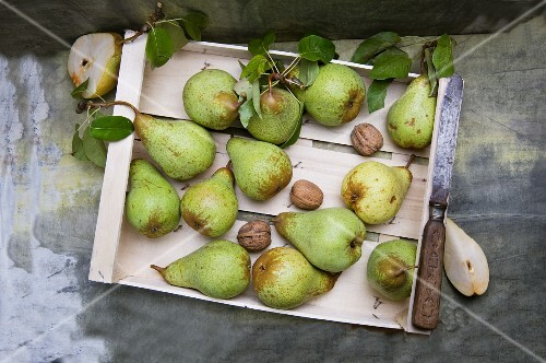 Pears and walnuts in a wooden crate