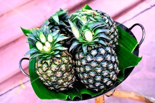 Fresh pineapple on banana leaves in a bowl