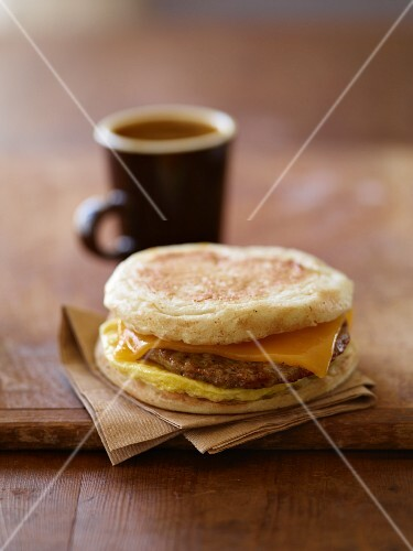 Sausage, Egg and Cheese Breakfast Sandwich on English Muffin; Cup of Coffee
