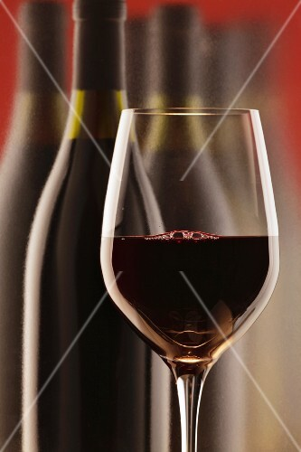 Glass of red wine in front of a bottle of red wine