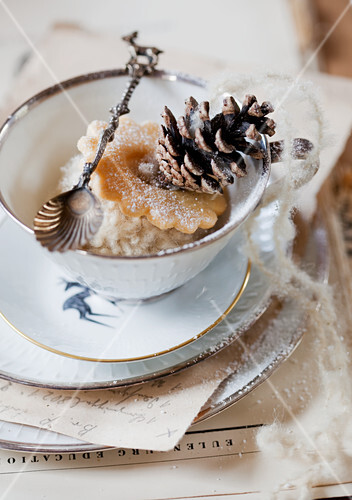 Biscuit, woollen pompom and pine cone in teacup