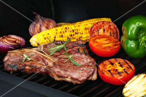Steak, vegetables and corn on the cob on a grill