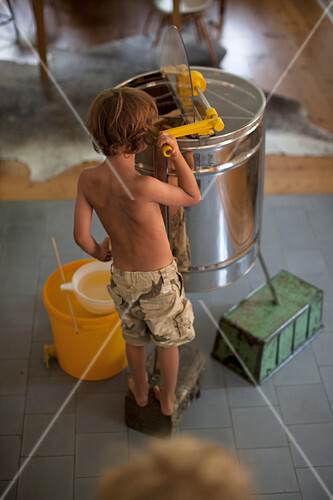 A boy standing by a honey extractor