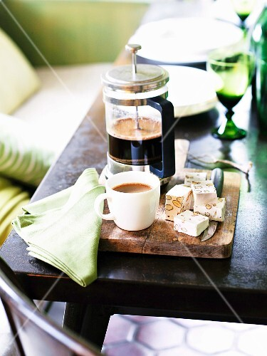 A cafetiere, coffee cups and nougat cubes on a wooden board on a table