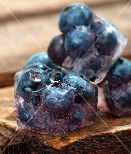 Ice cubes with blueberries on a wooden table