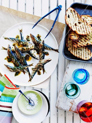 Grilled sardines and bread slices with chimichurri