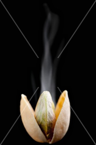A steaming, opened, toasted pistachio against a black background