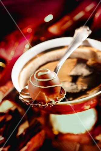 A praline on a spoon balanced over a coffee cup