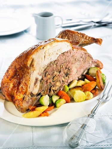 Half a stuffed turkey with oven-roasted vegetables