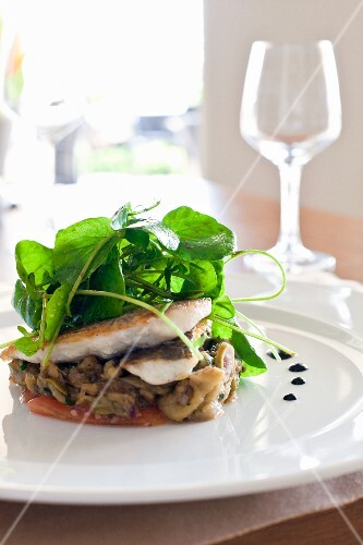 Sea bass on a bed of vegetables with water cress