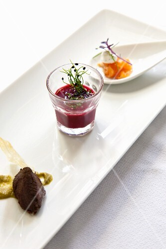 An appetizer platter with olive paste, beetroot soup and smoked salmon