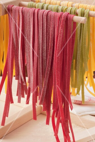 Colourful tagliatelle hanging to dry