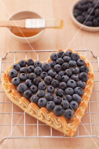 A heart-shaped blueberry tart on a wire rack