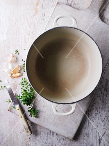 An empty bowl, herbs, garlic and a knife