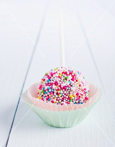 A cake pop decorated with sugar beads in a paper case