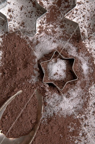 Cocoa powder on a silver spoon with sugar and biscuit cutters