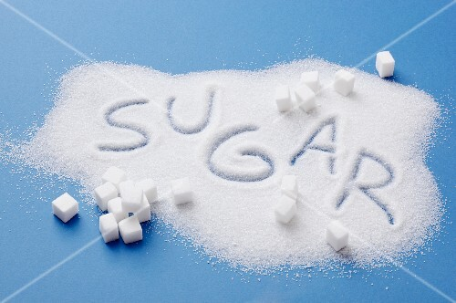 A pile of sugar with the word SUGAR written in it