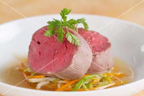 Pochiertes Filetsteak auf Gemüse und Brühe