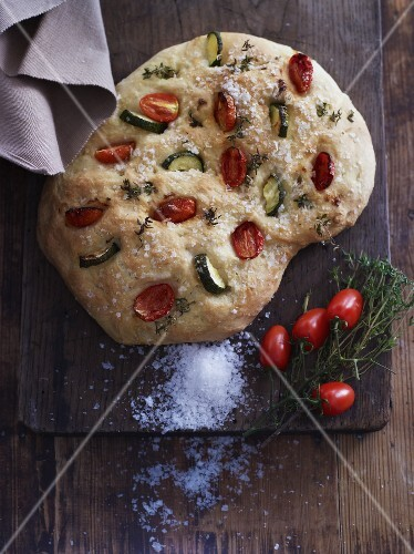 Focaccia with salt, plum tomatoes, courgettes and herb