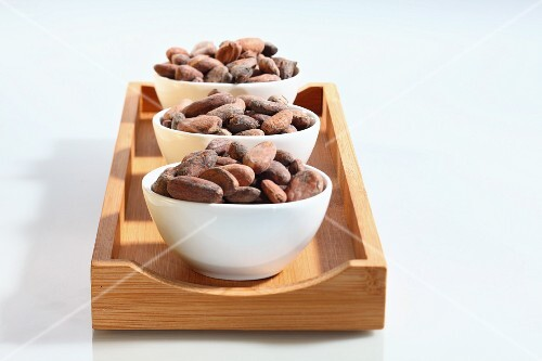 Three bowls of cocoa beans on a wooden board