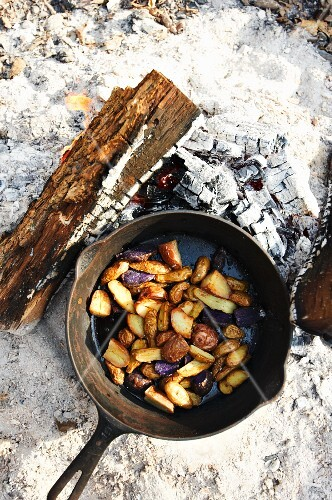 Roasted Potatoes Being Cooked in a Cast Iron Skillet Over an Open Fire