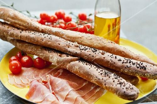 Bread sticks, raw ham and cherry tomatoes