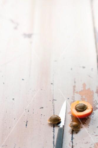 Halbierte Aprikose und Aprikosenkerne auf Holzuntergrund