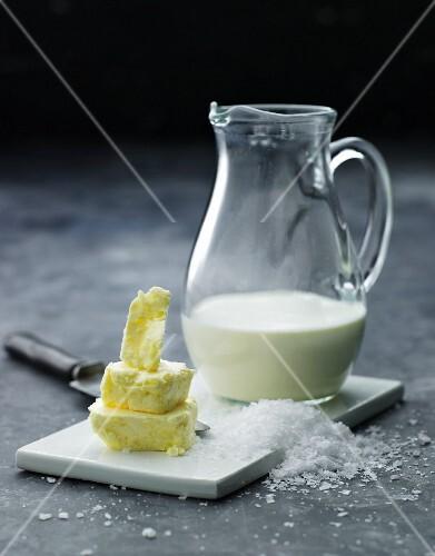 Stilleben mit Butterstückchen, grobem Salz & Milch im Glaskrug