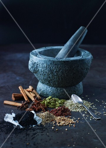 Various spices in front of a stone mortar