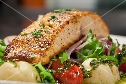 Salmon fillet on a bed of salad with tomatoes and potatoes